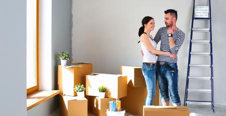 Glückliche junge Paare, die Kästen auspacken oder verpacken und in ein neues Haus umziehen Standard-Bild