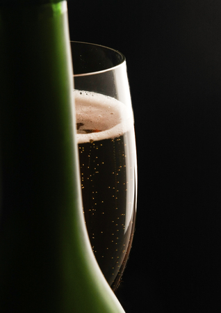 Glass of wine and a bottle on black background Banco de Imagens