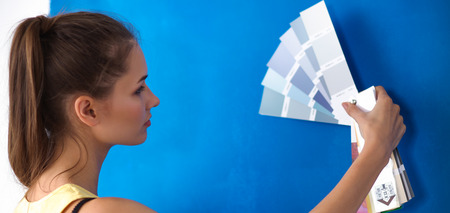Young beautiful woman holding color palette , standing near wall. Archivio Fotografico