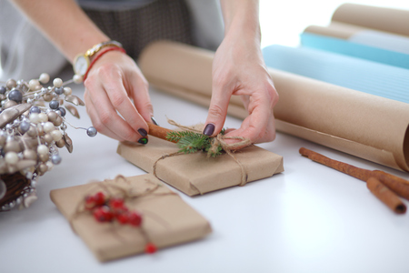 Hands of woman decorating christmas gift box. Hands of woman