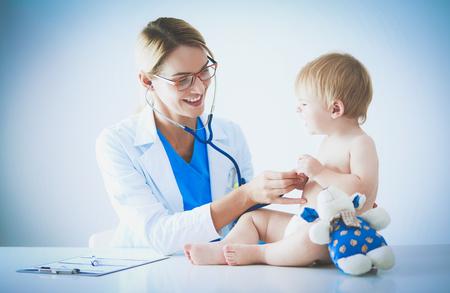 Doctora está escuchando niño con un estetoscopio en clínica