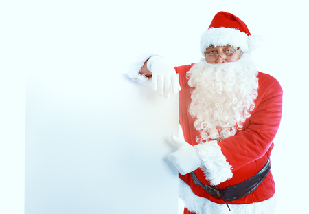 Happy Santa Claus looking out from behind the blank sign isolated on white background