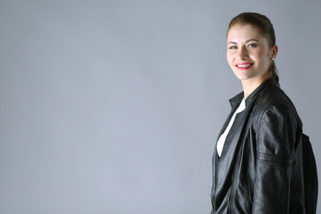 Portrait of beautiful young brunette woman in stylish black jacket on gray