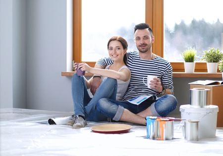 Portrait happy smiling young couple painting interior wall of new house. Young couple Stock Photo