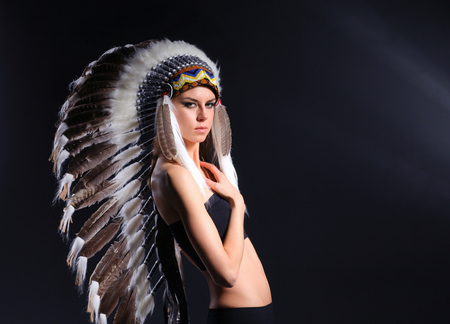 Beautiful woman in native american costume with feathers. Beautiful woman