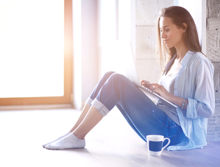 Young beautiful woman at home sitting on the floor with laptop. Young beautiful woman. Stock Photo