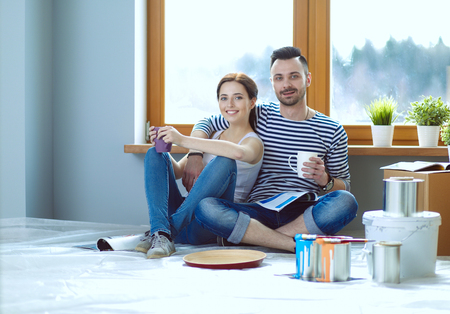 Portrait happy smiling young couple painting interior wall of new house. Young couple 스톡 콘텐츠
