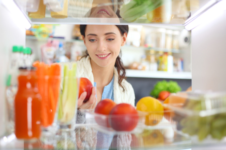 Portrait of female standing near open fridge full of healthy food, vegetables and fruits. Portrait of female Stock Photo
