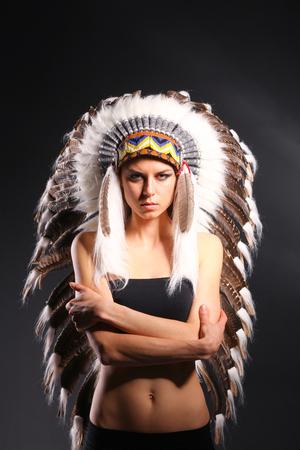 Beautiful woman in native american costume with feathers. Beautiful woman
