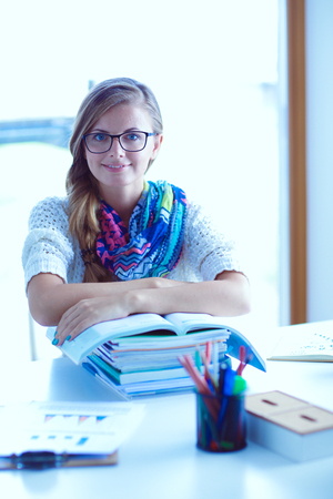 Young woman sitting at a desk among books. Student Stock Photo