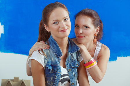 Two Beautiful young woman doing wall painting, sitting. Two Beautiful young woman. Фото со стока