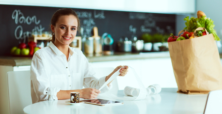 Young woman planning expenses and paying bills on her kitchen Foto de archivo