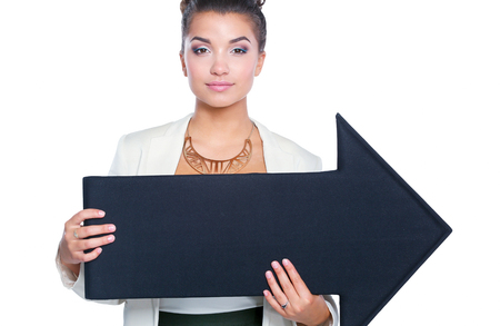 Beautiful young business woman holding a black arrows, over a white background