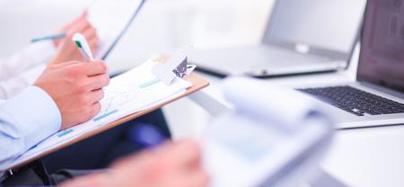 Zakenmensen zitten en schrijven op zakelijke bijeenkomst, in kantoor