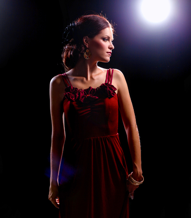 Young woman wearing a red dress standing