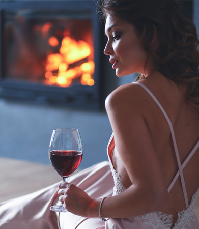 Sexy girl in front of the fireplace Stock Photo