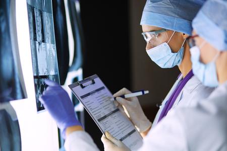 Twee vrouwelijke vrouwen medische artsen die röntgenstralen in het ziekenhuis bekijken