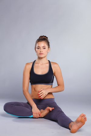 Young woman sitting on the floor in lotus position. yoga Standard-Bild