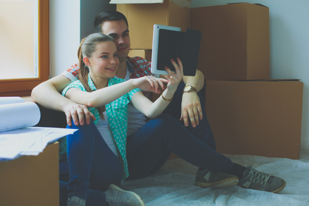 Couple moving in house sitting on the floor with ipad. Couple Stock Photo