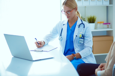 Doctor and patient couple are discussing something,sitting on the desk.