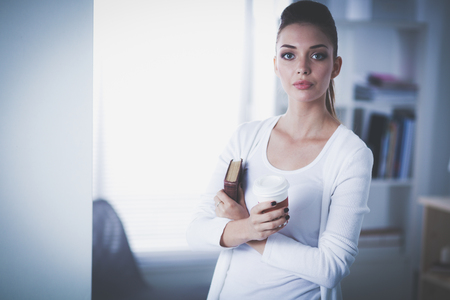 Attractive businesswoman standing near wall in office with book.