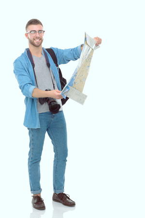 Young man holding at map on white background. Young man holding a map on a white background. A tourist on vacations. Looking for sights. Adventures seeker. Stock Photo
