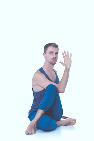 Adult man with naked torso doing exercise on white background
