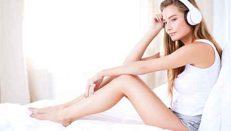 Portrait of beautiful woman in morning listening music sitting on bed at home Stock Photo