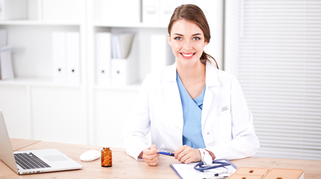 Beautiful young smiling female doctor sitting at the desk and writing.