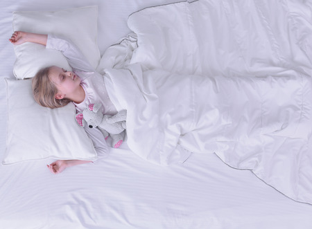 Child little girl sleeps in the bed with a toy teddy bear Stock Photo