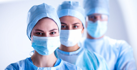 Surgeons team, wearing protective uniforms,caps and masks 스톡 콘텐츠