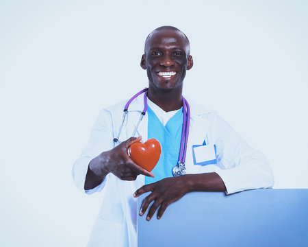 Male doctor with red heart and blank sign isolated on white background