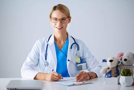 Beautiful young smiling female doctor sitting at the desk.