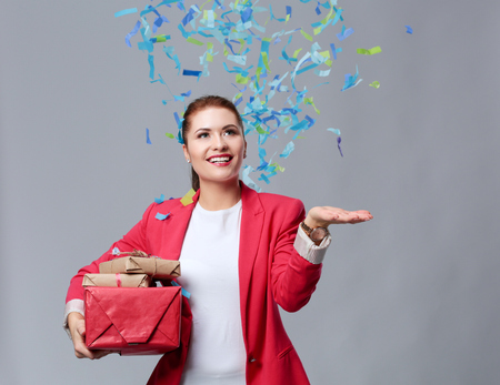Beautiful happy woman with gift box at celebration party with confetti . Birthday or New Year eve celebrating concept Stock Photo