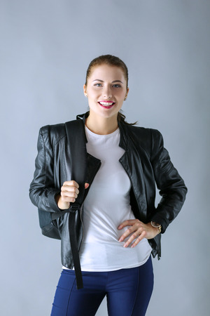 portrait of beautiful young brunette woman in stylish black jacket on gray.