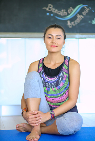 Portrait of smiling yoga woman sitting at yoga mat after workout at yoga studio. Yoga. Woman.