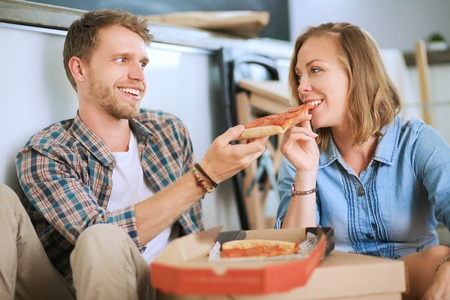 Young couple have a pizza lunch break on the floor after moving into a new home with boxes around them. Young couple Imagens