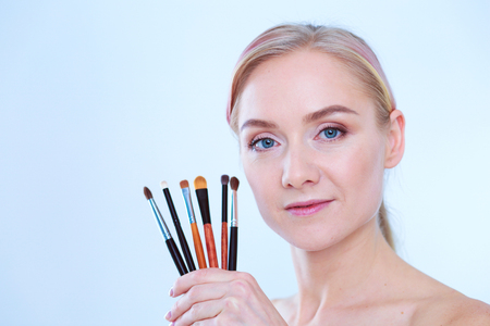 Portrait of beautiful young girl on white background with a perfect face with many hands holding makeup brush. Stock Photo