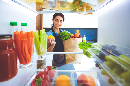 Portrait of female standing near open fridge full of healthy food, vegetables and fruits. Portrait of female Imagens