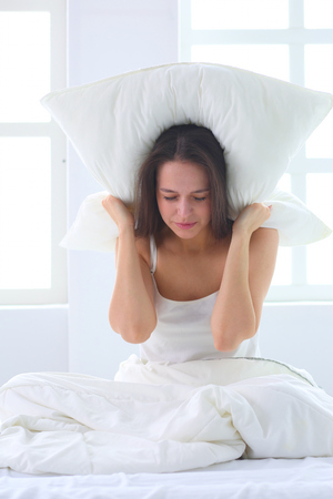 Young caucasian woman covering her head and ears with pillows Foto de archivo