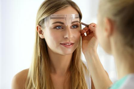 Maquillaje permanente para cejas. Primer plano de una mujer hermosa con cejas gruesas en un salón de belleza.