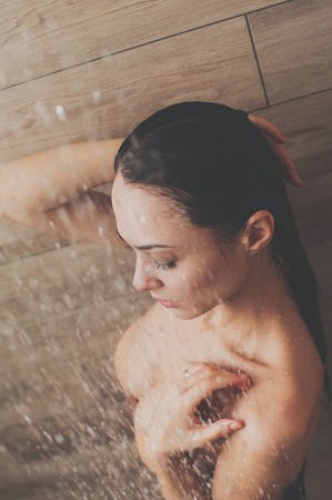Young beautyful woman under shower in bathroom. Stockfoto