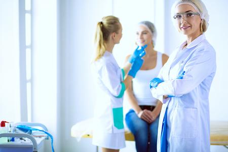 Beautiful woman face near doctor with syringe Foto de archivo