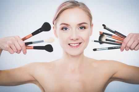 Portrait of beautiful young girl on white background with a perfect face with many hands holding makeup brush