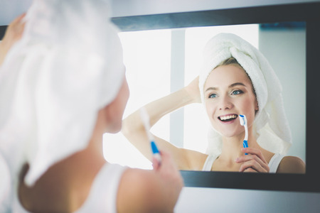 Young woman looking in mirror after brushing teeth Standard-Bild