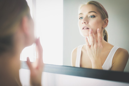 face of young beautiful healthy woman and reflection in the mirror Standard-Bild