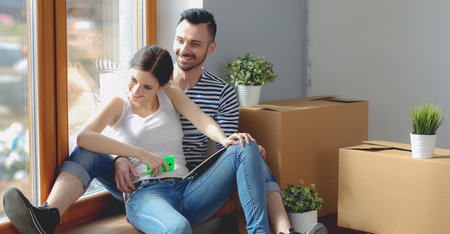 Couple moving in house sitting on the floor . Couple Imagens