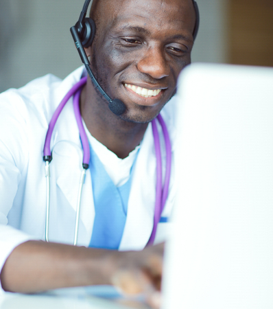 Portrait of young male doctor wearing headset while using computer at desk in clinic.