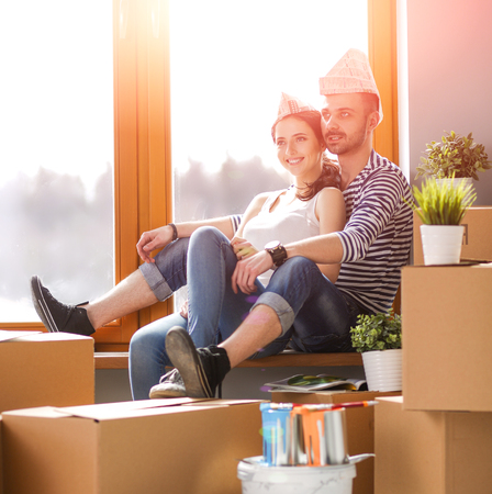 Couple moving in house sitting on the floor . Couple Stock Photo