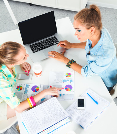 Two women working together at office, sitting on the desk Stock Photo